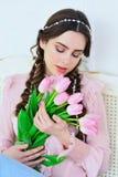 有郁金香花束的美丽的少妇 免版税图库摄影