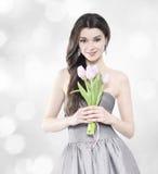 有郁金香花束的美丽的深色的妇女 库存照片