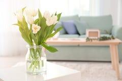 有郁金香花束的花瓶在桌上的 库存图片