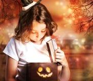 有配件箱的万圣节逗人喜爱的矮小的巫婆 库存照片