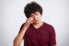 有酥脆头发的,磨擦疲乏的少年注视要睡觉,安排坏眼力,穿戴在红色偶然T恤杉,被隔绝在白色 图库摄影