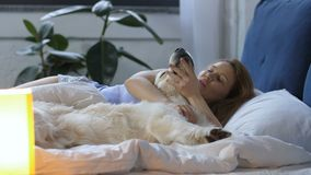 有醒在床上的拉布拉多狗的可爱的妇女 影视素材