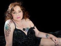 有醒目的金子的美丽的妇女注视与纹身花刺 免版税库存图片