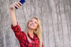 有采取在她的智能手机的美丽的面孔的年轻微笑的女孩自画象 她有金发,愉快的微笑 她佩带 免版税库存照片