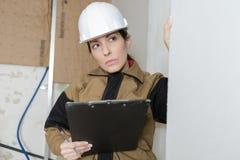 有采取笔记的安全帽的女性建筑师 库存照片