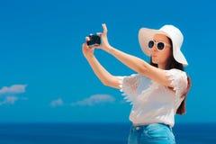 有采取Selfie的太阳帽子的逗人喜爱的夏天女孩在度假 免版税库存图片