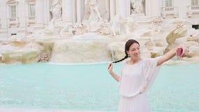 有采取selfie的巧妙的电话的少妇户外在欧洲城市在著名Fontana di Trevi附近 影视素材