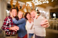 有采取selfie的智能手机的资深朋友在圣诞节时间 免版税库存图片