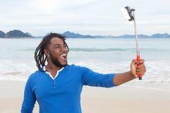 有采取selfie的dreadlocks的非裔美国人的人在海滩 免版税库存图片