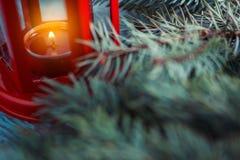 有里面一个被点燃的蜡烛的老红色灯笼和圣诞树 库存图片