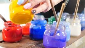 有里面明亮的油漆的五颜六色的玻璃瓶子 在瓶子的画笔 在近瓶子的许多不同的丙烯酸漆对a 股票视频