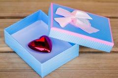 有里面桃红色弓和心脏的蓝色礼物盒 库存照片