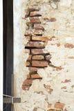 有里面橙色砖的破裂的水泥墙壁 库存图片
