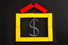有里面美元的符号的木玩具房子 免版税库存图片