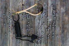 有重点的弹弓在暗色老木板说谎与深刻的纹理的与金属球一起 库存图片