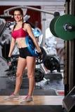 有重的圆盘的少妇在健身房 库存照片