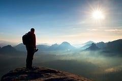 有重的背包和三脚架的单独摄影师在手中在岩石峭壁和观看下来对深刻的有薄雾的谷轰鸣声 免版税库存照片