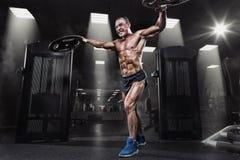 有重量盘的专业爱好健美者在健身房 举重运动员w 免版税库存图片