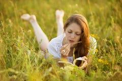 有野花书的女孩  库存照片