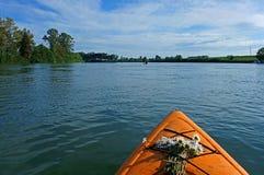 有野花的皮船在农村河 免版税库存图片