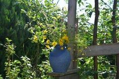 有野花的蓝色花瓶在庭院里 免版税库存图片