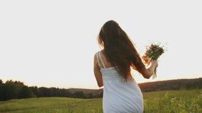 有野花花束的妇女在领域跑在日落,享受自由在阳光的草甸点燃 股票视频