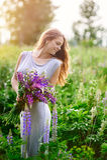 有野花花束的美丽的妇女在草甸 库存照片