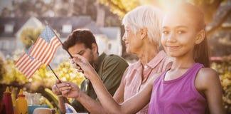 有野餐和采取美国国旗的愉快的家庭 免版税库存照片