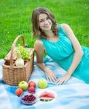 有野餐篮子的美丽的微笑的妇女和果子在夏天 免版税库存照片