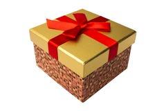有金上面和一条红色丝带的礼物盒 免版税库存图片