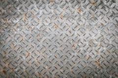 有金刚石样式和生锈的背景的老金属底板 免版税库存照片