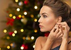有金刚石耳环的美丽的妇女在圣诞节 免版税库存照片