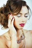 有金发卷曲发型的年轻俏丽的妇女在白色后面 免版税库存图片