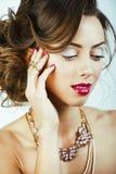 有金发卷曲发型的年轻俏丽的妇女在白色后面 免版税库存照片