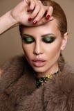 有金发和明亮的构成的妇女,在有珠宝的典雅的皮大衣 免版税库存照片