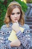 有金发和蓝眼睛的美丽的女孩在他的手上的拿着一本书 库存图片