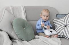 有金发和蓝眼睛的逗人喜爱的婴孩坐沙发和 免版税图库摄影