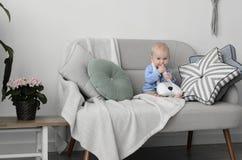 有金发和蓝眼睛的逗人喜爱的婴孩坐沙发和 库存图片