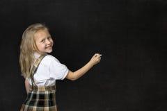 有金发微笑的愉快的文字的年轻甜小辈女小学生与在黑板的白垩 免版税库存图片