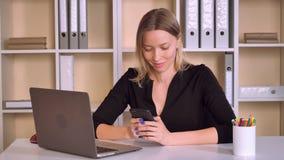 有金发用途巧妙的电话的美丽的工作者 股票录像