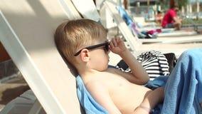 有金发的一个小男孩在太阳懒人的太阳镜晒日光浴 股票录像