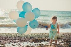 有金发的享受夏时假日的婴孩逗人喜爱的女孩和桃红色苹果面颊摆在沙子使与蓝色白色bal的海边靠岸 库存图片
