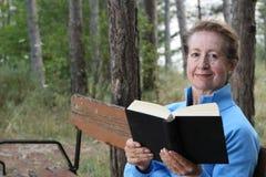 有金发的典雅的成熟妇女读一本书的外面在有拷贝空间的公园 库存图片