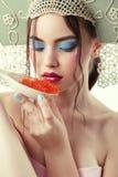 有金发的华美的妇女在俄国全国帽子吃鱼子酱 库存图片