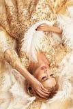 有金发的华美的性感的妇女在豪华米黄礼服 免版税库存照片