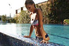 有金发的女孩在放松在游泳池的典雅的比基尼泳装 库存图片