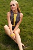 有金发的女孩在游泳衣,放松在夏天庭院里 免版税库存图片