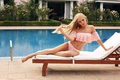 有金发的女孩在游泳衣,松弛近的游泳的po 免版税库存图片