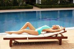 有金发的女孩在游泳衣,松弛近的游泳的po 免版税图库摄影