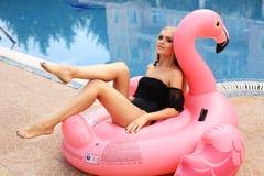 有金发的女孩在游泳衣,松弛近的游泳的po 图库摄影